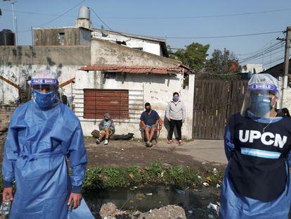 Dos trabajadores sanitarios, a principios de agosto con vecinos de Villa Fiorito (Buenos Aires, Argentina).
