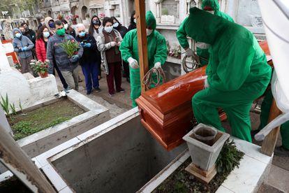 Trabajadores del cementerio de Colina, en las afueras de Santiago, manipulan el ataúd de un hombre de 68 años que murió víctima de la covid-19.