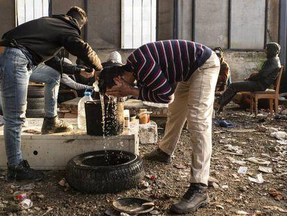 Migrantes argelinos se lavan con una garrafa de agua en una nave industrial el pasado enero, en Velika Kladuša, una ciudad cercana al campo de Bihac, las dos en Bosnia y Herzegovina.
