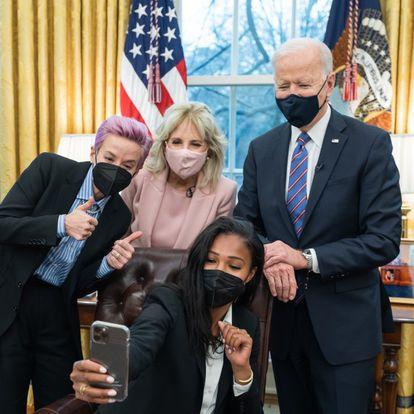 """El presidente Joe Biden y la primera dama Jill Biden posan para una foto con las jugadoras de fútbol de la Selección Nacional Femenina de Estados Unidos, Megan Rapinoe y Margaret """"Midge"""" Purce, el 24 de marzo en el Despacho Oval."""