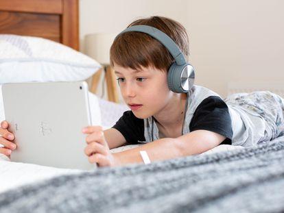 Un niño usa una tablet en su dormitorio.