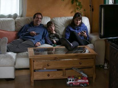 Una familia ve la televisión en el salón de su casa.