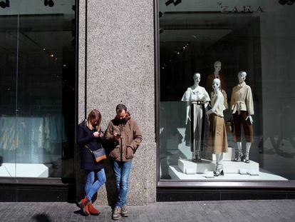 Un hombre y una mujer miran su móvil a las puertas de una tienda de Zara en Madrid