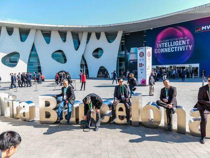 Asistentes al Mobile World Congress de 2019 se toman un descanso en los exteriores de la Fira de Barcelona.
