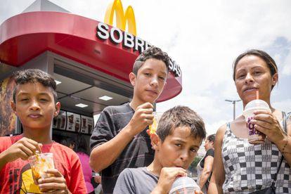 Susi, una cuidadora de 33 años, lleva a sus hijos, Vitro, de 14, Wesley y Diogo, ambos de 10, a su primera visita al McDonald's de Cidade Tiradentes.