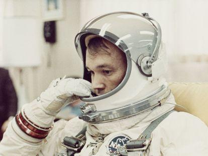 El piloto Michael Collins se ajusta el casco de su traje espacial en la sala de preparación de Cabo Kennedy, en Florida, antes de la misión Gemini 10 de la NASA, en julio de 1966.