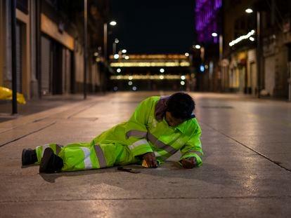 Rita Gutiérrez, tumbada en el suelo, quita un chicle pegado en la calle Madero, este jueves.