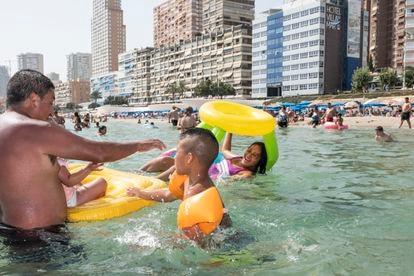 Mario Baltodano (izquierda) juega el sábado en el agua de la playa de Benidorm con Alexander (centro) y Andrea (subida en el flotador).