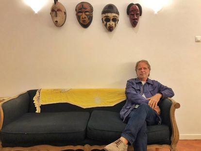 El escritor mozambiqueño Mía Couto posa bajo una colección de máscaras africanas en Maputo.