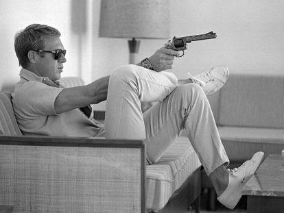 Steve McQueen, sentado en el sofá de su casa de Palm Springs (California) con una pistola en la mano, en mayo de 1963.