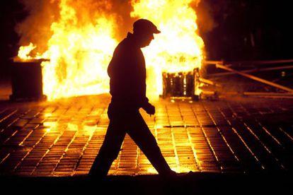 Un hombre pasa una barricada de fuego hoy en Bucarest (Rumanía).