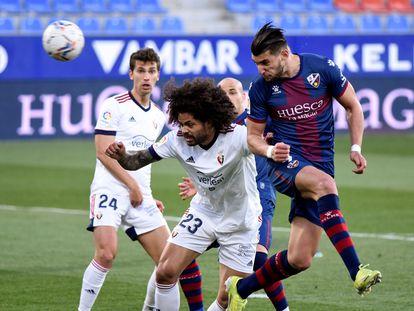 Rafa Mir cabecea el balón ante la presión de Aridane en el partido entre el Huesca y Osasuna este sábado en el Alcoraz.
