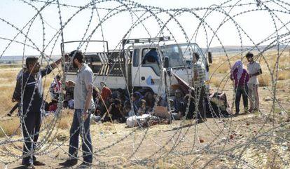Varios kurdos esperan en la frontera turca después de haber escapado de Kobane (Siria).