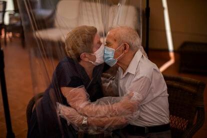 Agustina Cañamero, de 81 años, y Pascual Pérez, de 84, se abrazan y besan a través de una pantalla de película plástica para evitar contraer el nuevo coronavirus en un asilo de ancianos en Barcelona, España, el lunes 22 de junio de 2020,en el centro de ancianos Ballesol Fabra i Puig.