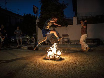 Un niño saltando la hoguera de la noche del 23 de junio en la colonia del Manzanares.