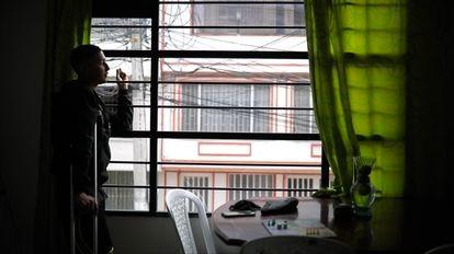 Diego Barceló fuma un cigarrillo desde la ventada de su casa en Bogotá.