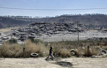 Un niño camina en el barrio de Escalerillas con el basurero municipal al fondo en Chimalhuacan, Estado de México.