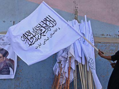 Un vendedor sostiene una bandera de los talibanes junto a una imagen del mulá Baradar, en Kabul. AAMIR QURESHI / AFP