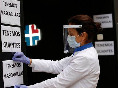 Una farmacéutica de Terrassa (Barcelona) coloca carteles para anunciar que en la farmacia venden mascarillas y guantes, el pasado jueves.