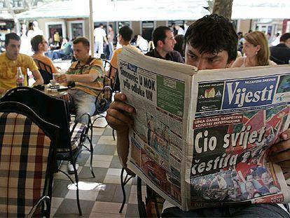 """Un hombre lee un periódico con el titular """"El mundo entero se congratula"""", ayer en Podgorica."""