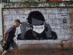 A man walks past a graffiti of Brazil's President Jair Bolsonaro wearing a protective mask during the new coronavirus outbreak in Rio de Janeiro, Brazil, Tuesday, April 7, 2020. (AP Photo/Silvia Izquierdo)