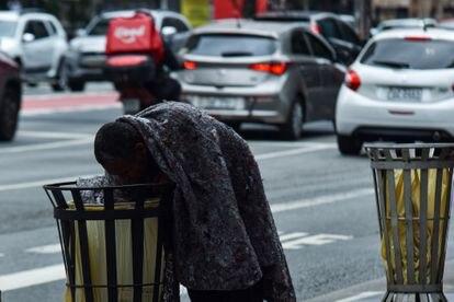 Un indigente busca comida en una papelera de la Avenida Paulista de São Paulo el 29 de junio.