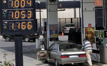 Un hombre reposta carburante en su coche en una estación de servicio.