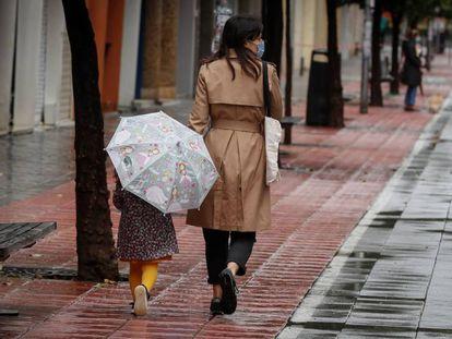 Una madre pasea con su niña por la calle Asunción de Sevilla.