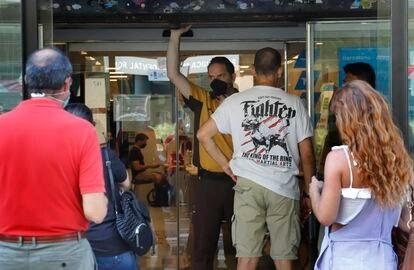 Un guardia de seguridad custodia la entrada de una oficina del Sepe en Barcelona.