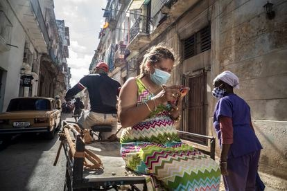 A woman looks at her mobile phone while riding a bicycle cart in Havana, Cuba,