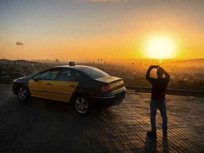Barcelona. Un taxista de la capital catalana toma fotografías del perfil urbano desde lo alto del monte Tibidabo al amanecer.