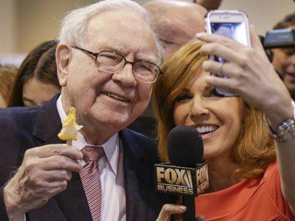Warren Buffett posa para una foto con una periodista en la junta de Berkshire Hathaway.