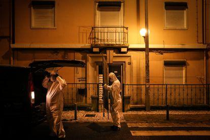 Trabajadores de una funeraria se preparan para recoger un cuerpo en Amadora el 30 de enero.