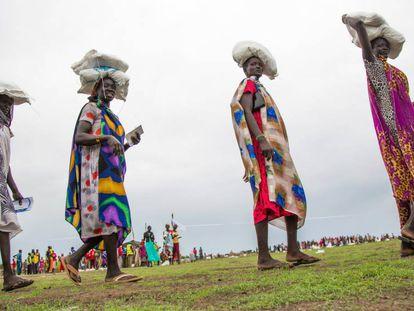 Varias mujeres transportan sacos de comida repartidos por el Programa Mundial de Alimentos el 23 de mayo de 2017 en Ganyiel, Sudán del Sur.