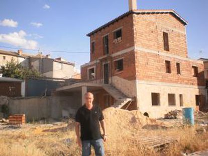 El alcalde de Olmeda de la Cuesta (Cuenca), José Luis Regacho, posa delante de una de las parcelas subastadas en la que su nuevo dueño ya se está construyendo una vivienda.