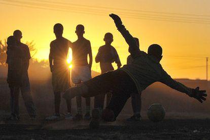 Chicos de Sudáfrica juegan al fútbol en Bloemfontein. Los expertos analizarán si organizar el Mundial aporta beneficios duraderos.