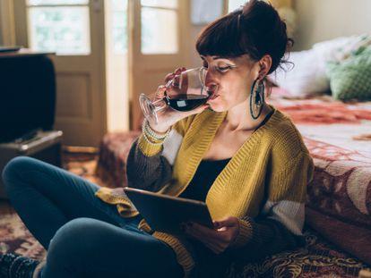 Una mujer bebe una copa de vino.