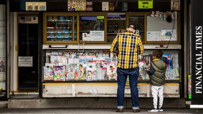 Un padre con su hijo en un quiosco de prensa en las inmediaciones del hospital La Paz.