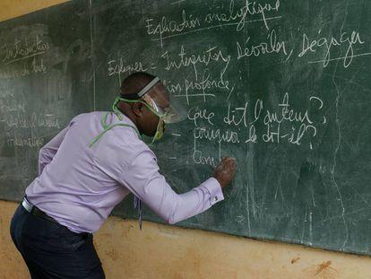 Un profesor da clase, con un sistema de protección, en un aula de Camerún.