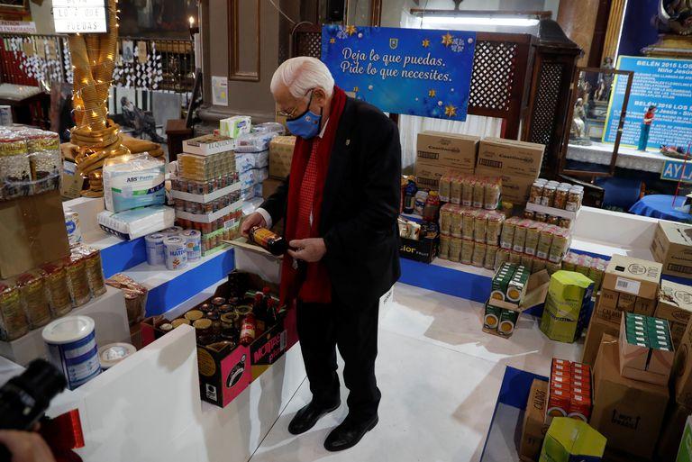 El padre Ángel, rodeado de cajas con alimentos en la Iglesia de San Antón de Madrid para el Banco de Alimentos.