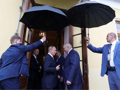Putin y Lukashenko, resguardados bajo paraguas, en San Petersburgo en julio de 2019. (