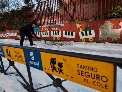 Un familiar colabora en la limpieza del hielo y la nieve en las inmediaciones del colegio Amadeo Vives.