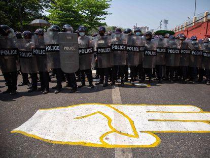 Policías en Yangón bloquean este jueves una calle donde se ha pintado el saludo de los tres dedos convertido en símbolo de las protestas contra el golpe de Estado en Myanmar.