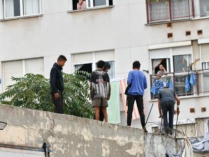 Un policía nacional trabaja para que un grupo de menores migrantes abandone el tejado de una nave industrial donde habían sido alojados, el pasado 27 de agosto en Ceuta.