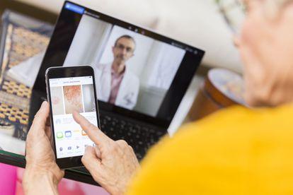 Una mujer consulta su móvil durante una consulta de telemedicina.