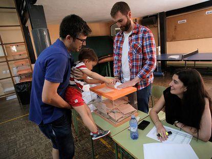 Un niño mete en la urna el voto de su padre en un colegio de Guzmán el Bueno de Madrid. 36.518.100 electores están llamados este domingo a votar, por segunda vez en seis meses, por la incapacidad de los partidos para llegar a un acuerdo de gobierno.