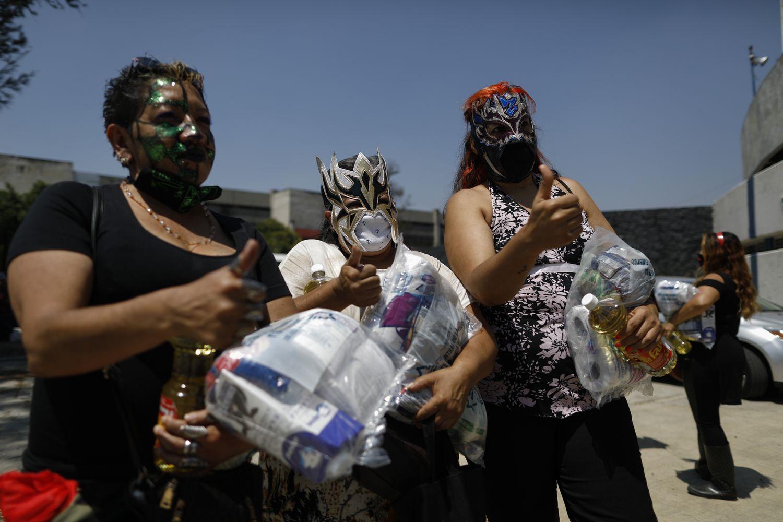 Las luchadoras Migala, La Fugitiva, y La Zorra, tras recoger una de las ayudas por parte del Comité de lucha libre de Ciudad de México.