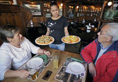 Una camarera sirve a dos clientes en el restaurante Pizzbur en Covas (Viveiro).