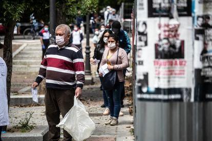 Cola de personas esperando para recibir alimentos del comedor social en la parroquia San Ramón Nonato en Puente de Vallecas.