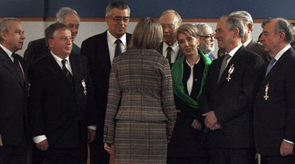 La ministra de Defensa, Carme Chacón, de espaldas, charla con la viuda del teniente coronel García Márquez rodeada de militares de la UMD condecorados ayer.